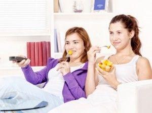 Girls eating and watching TV/freedigitalphotos