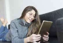 Portrait of smiling young woman lying on couch using earphones and digital tablet